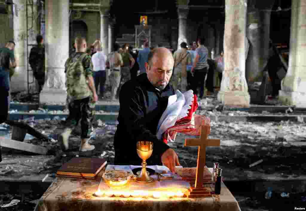 Seorang pria Kristen Irak menyiapkan misa pertama di gereja Grand Immaculate Church kota Qaraqosh, dekat Mosul, setelah kota ini dibebaskan dari cengkeraman ISIS.