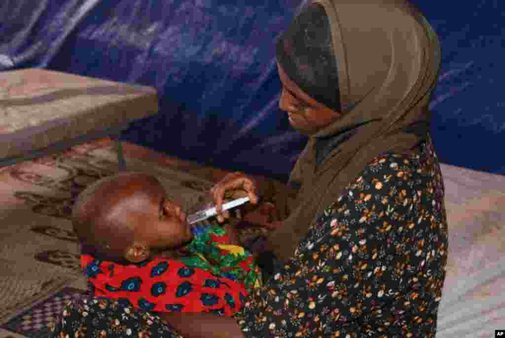 A woman feeds her malnourished child with a syringe at Hilaweyn Refugee Camp health center. VOA - P. Heinlein