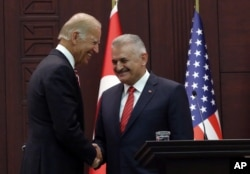 FILE - U. S. Vice President Joe Biden, left, and Turkish Prime Minister Binali Yildirim shake hands after a joint news conference in Ankara, Turkey, Aug. 24, 2016.