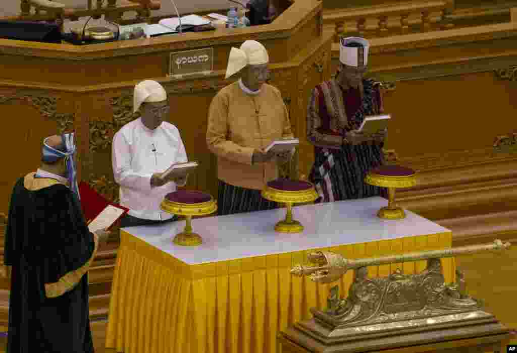 Htin Kyaw, second right, takes oaths as Myanmar's new president during a sworn-in ceremony in Myanmar's parliament in Naypyitaw.