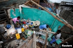 Residents work clearing a house destroyed by Hurricane Matthew in Les Cayes, Haiti, Oct. 5, 2016.