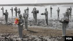 Patung-patung manusia lumpur di area tanggul kolam penampungan lumpur Lapindo, Rabu (28/5), menandai peringatan delapan tahun tragedi semburan lumpur panas. (VOA/Petrus Riski)