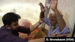Dr. Shaikot Majumder examines Abdu Zabber, who says he feels pain across his body.