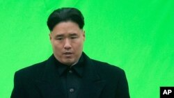 """FILE - An actor playing North Korean leader Kim Jong Un waits ahead of filming for the movie """"The Interview,"""" at Robson Square in Vancouver, British Columbia."""