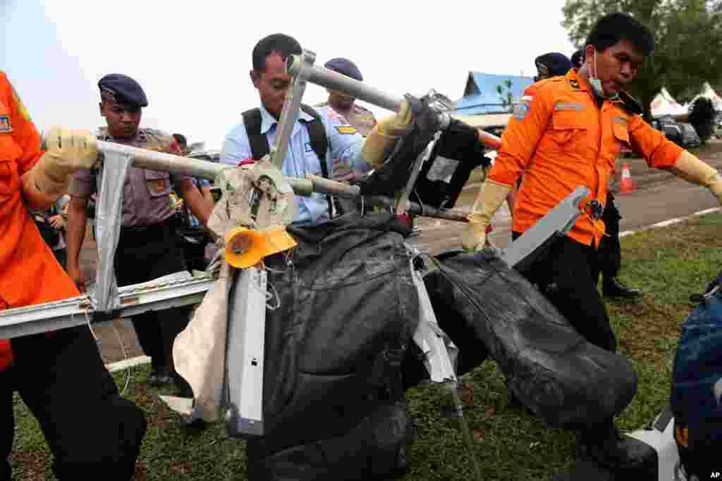Anggota Badan SAR Nasional (Basarnas) mengangkat tempat-tempat duduk pesawat AirAsia bernomor penerbangan 8501 setelah diangkut oleh helikopter Angkatan Udara AS di bandar udara Pangkalan Bun (5/12). (AP/Tatan Syuflana)