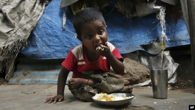 An Indian child eats midday meal organized by Andhra Pradesh government at a shanty area in Hyderabad, India, Jan. 11, 2012.