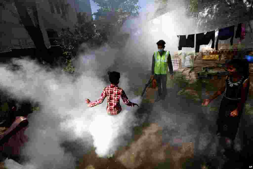 A boy plays smoke from fumigation being carried out by a municipal worker at a residential area in Ahmedabad, India.
