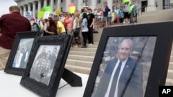FILE - Family photographs of Joshua Holt, an American jailed in Venezuela, are part of a rally at the Utah State Capitol, July 30, 2016, in Salt Lake City. Holt was arrested on suspicion of weapons charges after he traveled to Venezuela on a tourist visa to marry a fellow Mormon he met on the internet.