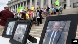 FILE - Family photographs of Joshua Holt, an American jailed in Venezuela, are part of a rally at the Utah State Capitol in Salt Lake City, July 30, 2016.