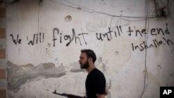 """Un rebelde sirio en el distrito Amariya de Alepo. Fuerzas del gobierno y sus aliados cerraron hace poco la única vía hacia zonas bajo control rebelde en la ciudad. La leyenda en la pared dice """"Lucharemos hasta el final. Si Dios quiere""""."""