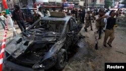 Tentara dan petugas kepolisian menghalau warga untuk menjauhi lokasi ledakan bom di Karachi (26/6). Ledakan yang menarget hakim teras Pengadilan Tinggi Sindh, Maqbool Baqir ini menewaskan sedikitnya tujuh orang dan menciderai 15 lainnya, termasuk Hakim Baqir.