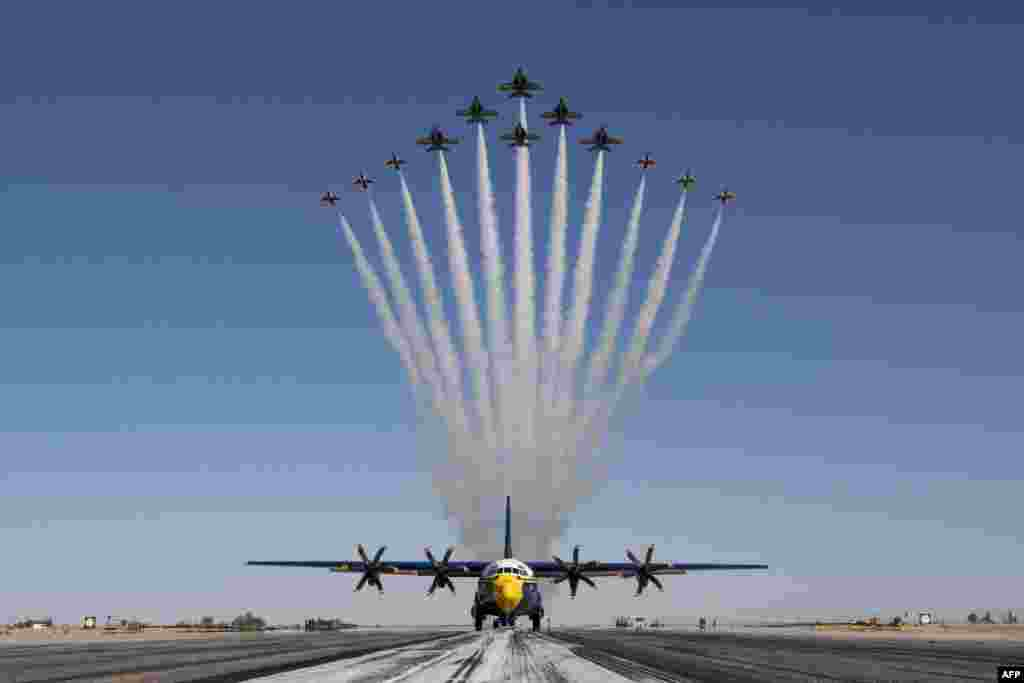 "This handout photo of the U.S. Air Force shows the U.S Air Force Air Demonstration Squadron ""Thunderbirds"" and the U.S. Navy Flight Demonstration Squadron ""the Blue Angels"" debut the Super Delta formation over a C-130J Super Hercules at Naval Air Facility El Centro, March 2, 2021."