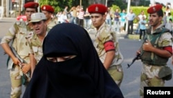 FILE - An Egyptian woman is seen in front of a group of soldiers as they stand guard during a protest near Cairo University.