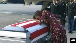FILE - In this frame from video, Myeshia Johnson cries over the casket in Miami, Florida, Oct. 17, 2017, of her husband, Sgt. La David Johnson, who was killed in an ambush in Niger.