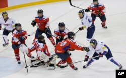 FILE - South Korea's Lee Eun-ji, bottom right, scores a goal as North Korea's Kim Kum Bok, bottom second right, tries to block the puck during their IIHF Ice Hockey Women's World Championship Division II Group A game in Gangneung, South Korea, April 6, 2017.