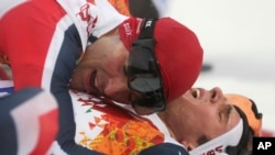 Norway's Joergen Graabak (r) is congratulated by Norway's silver medal winner Magnus Hovdal Moan after winning the gold medal during the Nordic combined individual large hill competition at the 2014 Winter Olympics, Feb. 18, 2014, in Krasnaya Polyana, Rus