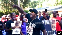In this May 5, 2020, photo, Keith Smith speaks to a crowd as they march through a neighborhood in Brunswick, Ga. They were demanding answers regarding the death of Ahmaud Arbery.