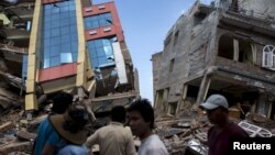 People walk past a collapsed building after a fresh 7.3 earthquake struck, in Kathmandu, Nepal, May 12, 2015.