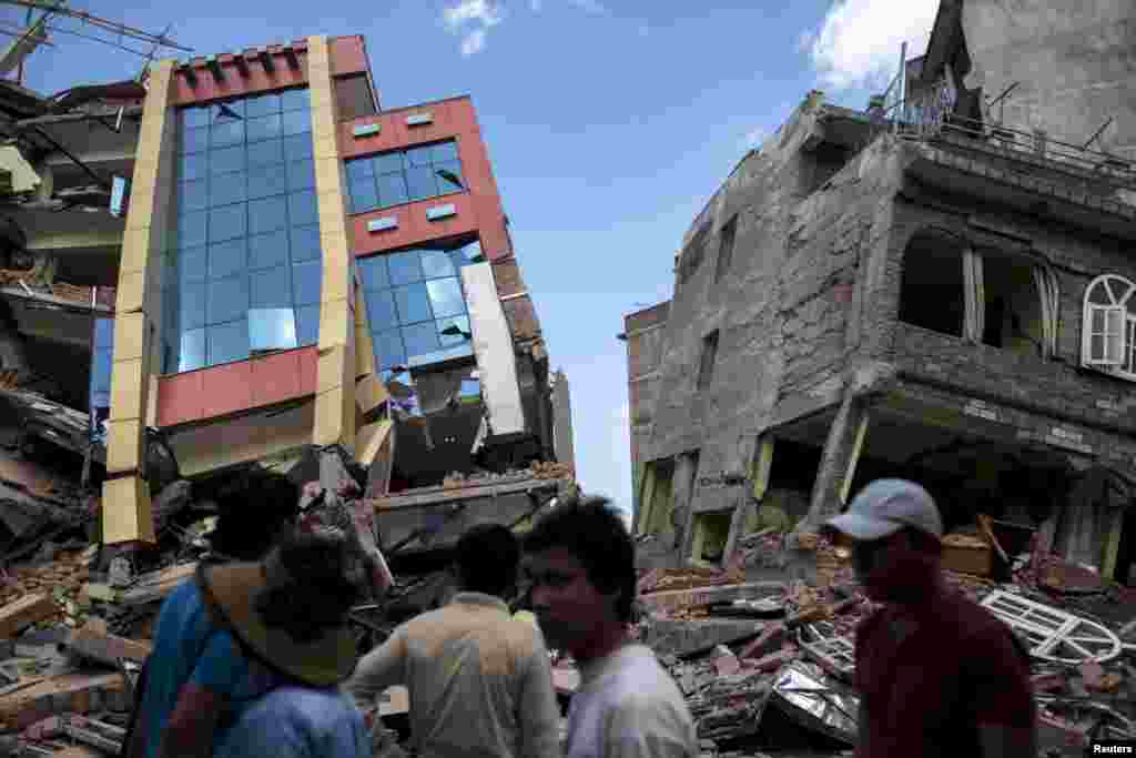 People walk past a collapsed building after a 7.3-magnitude earthquake struck, in Kathmandu, Nepal.