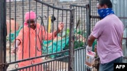 A volunteer from the Rays of Light NGO delivers food and cleaning products to an elderly woman living alone in Alexandra, Johannesburg, on April 16, 2020.