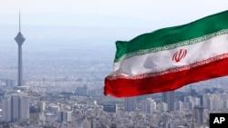Bendera nasional Iran berkibar tertiup angin saat menara dan gedung telekomunikasi Milad terlihat di latar belakang, Teheran, Iran, 31 Maret 2020. (Foto: AP)