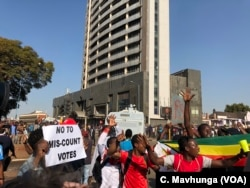 FILE - Protesters argue that election results are false and that opposition leader Nelson Chamisa is the true winner, in Harare, Aug. 1, 2018.