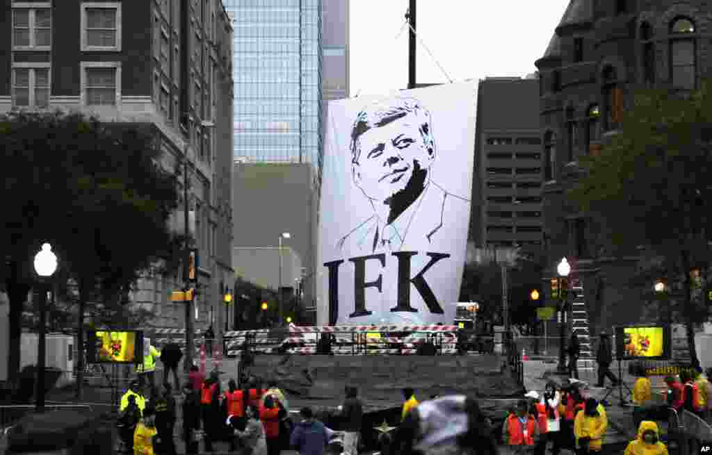 A banner of John F. Kennedy is lowered to the stage before a ceremony to mark the 50th anniversary of his assassination, near Dealey Plaza in Dallas, Texas, Nov. 22, 2013.