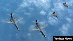 20일 한반도 상공에서 미 공군 B-1B 전략폭격기(왼쪽)가 한국 공군 F-15K 전투기의 엄호를 받으며 비행하고 있다.