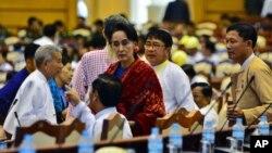 ຜູ້ນຳພັກສັນນິບາດແຫ່ງຊາດເພື່ອປະຊາທິປະໄຕ ຫຼື National League for Democracy party (NLD) ທ່ານນາງ Aung San Suu Kyi, ຕຸ້ມຜ້າສີແດງ ໃນກອງປະຊຸມທີ່ນະຄອນຫຼວງ Naypyitaw ປະເທດ Myanmar.