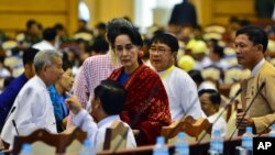 FILE - NLD leader Aung San Suu Kyi, covered in a red scarf, stands among the lawmakers of her party ahead of a regular session of Myanmar's lower house of parliament in Naypyidaw, Jan. 7, 2016.