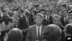 FILE - In this June 7, 1966, file photo Sen. Robert F. Kennedy is surrounded by students and newsmen as he tours Stellenbosch, South Africa, during a five-day visit to South Africa as the guest of the multiracial National Union of South African students.