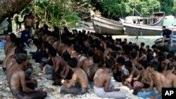Para pengungsi Rohingnya duduk di tanah saat ditangkap oleh Angkatan Laut Thailand di laut Andaman, 12 Desember 2008 (Foto: dok).
