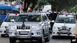 FILE - In this Oct. 18, 2014 file photo, former chief minister of India's Tamil Nadu state Jayaram Jayalalitha travels in a car accompanied by a row of cars with red beacon lights after being released from a prison in Bangalore, India.