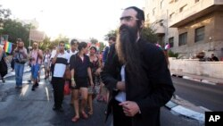 FILE - Ultra-Orthodox Jew Yishai Schlissel walks through a Gay Pride parade prior to pulling a knife from under his coat and stabbing people in Jerusalem, July 30, 2015.