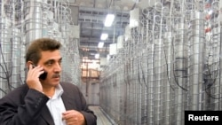 FILE - An official from Iran's Atomic Energy Organization stands in front of uranium enriching centrifuges at a 2009 an exhibition of Iran's nuclear achievements at Shahid Beheshti University in Tehran.
