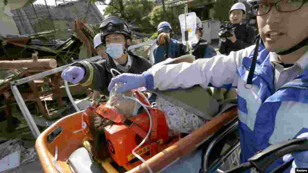 A woman is carried away by rescue workers after being rescued from her collapsed home caused by an earthquake in Mashiki town, Kumamoto prefecture, southern Japan, in this photo taken by Kyodo, April 16, 2016.