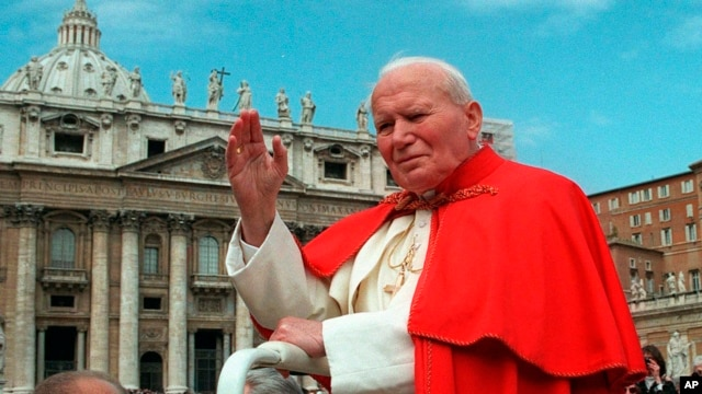 FILE - In this file photo taken on April 23, 1997, Pope John Paul II waves to faithful as he crosses St. Peter's Square at the Vatican.