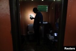 Ana Perez uses a solar lamp inside the bathroom of her home, Jan. 26, 2018, after Hurricane Maria damaged the electrical grid in Sept. 2017, in Naguabo.