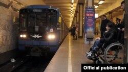 Əlil arabasında metroda hərəkət edən insan