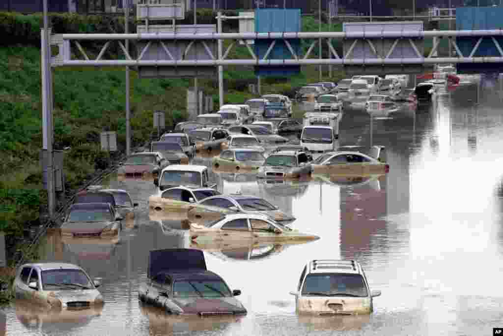 July 28: Vehicles are submerged in floodwater after heavy rain in Seoul, South Korea. Thousands of rescuers used heavy machinery and shovels Thursday to clear mud and search for survivors after huge landslides and flooding killed more than 40 people. (AP