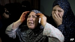 Palestinian mourners weep during the funeral of two-year-old, Rahaf Hassan, and her 30-year-old pregnant mother, Noor Hassan, who were killed in an Israeli air strike Sunday morning, during their funeral in the family house south of Gaza city in the Gaza
