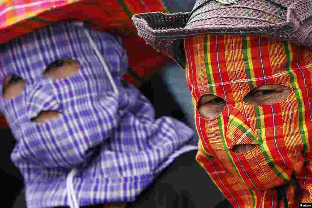 Farmers wearing face masks protest outside the temporary office of Thai Prime Minister Yingluck Shinawatra in Bangkok.