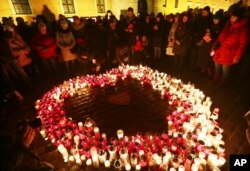 People stand by a heart shaped with candles as a tribute to slain mayor of Gdansk Pawel Adamowicz at the Square in the Old Town, Warsaw, Poland, Jan. 16, 2019.
