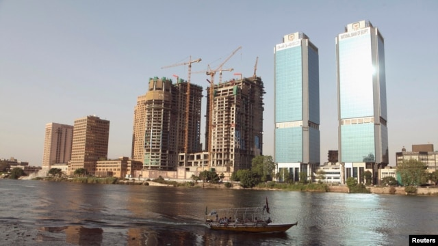 A boat passes buildings under construction and the two towers of the Bank of Egypt building (R), overlooking the river Nile in Cairo, June 7, 2013.