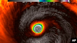This false-color satellite image provided by the National Oceanic and Atmospheric Administration (NOAA) shows the moment the eye of Super Typhoon Yutu passed over Tinian, one of three main islands in the U.S. Commonwealth of the Northern Mariana Islands, producing damaging winds and high surf Oct. 24, 2018.