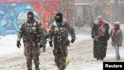 Polisi pasukan khusus berpatroli di daerah pertokoan Istiklal di tengah salju di pusat kota Istanbul, Turki (9/1). (Reuters/Murad Sezer)