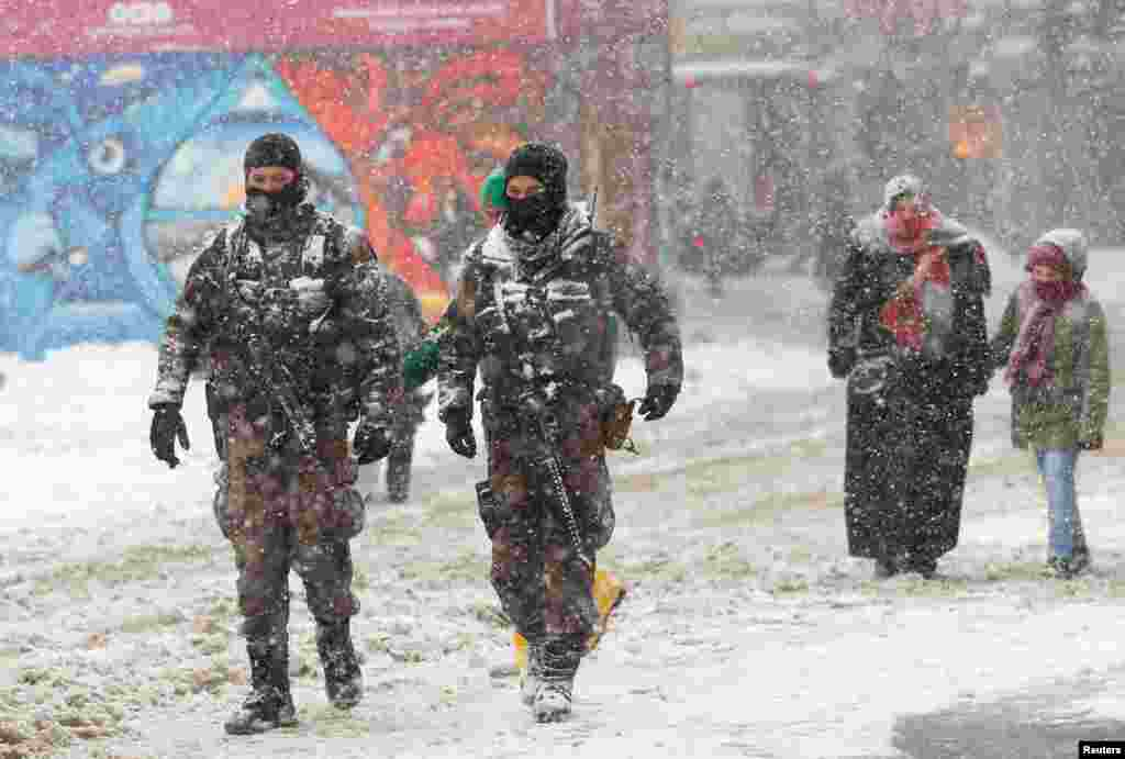 Members of police special forces walk along the main shopping and walking street of Istiklal during a snowfall in central Istanbul, Turkey.