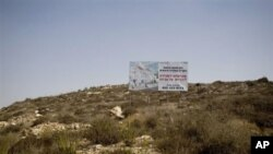 A sign advertising a planned housing project stands in the West Bank Jewish settlement of Ariel, 05 Oct 2010