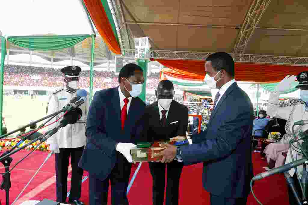 O Presidente cessante da Zâmbia, Edgar Chagwa Lungu, à direita, entrega os instrumentos do poder ao seu sucessor, o Presidente Hakainde Hichilema, durante a cerimónia de inauguração no Estádio Heróis em Lusaka, Zâmbia, terça-feira, 24 de Agosto de 2021.