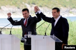 FILE - Greek Prime Minister Alexis Tsipras and Macedonian Prime Minister Zoran Zaev gesture before the signing of an accord to settle a long dispute over the former Yugoslav republic's name in the village of Psarades, in Prespes, Greece, June 17, 2018.